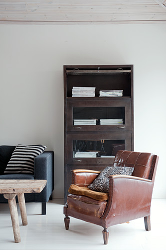 Worn leather armchair in front of vintage office cabinet with fold-down glass doors and rustic wooden table in front of modern sofa