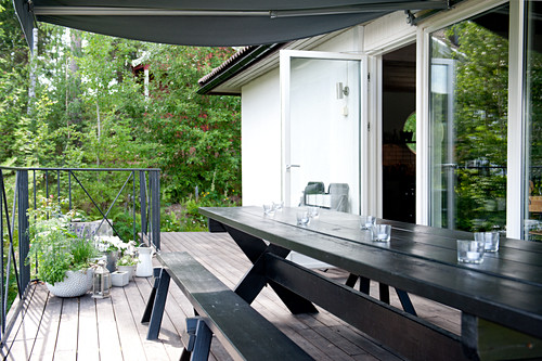 Rustic, black-painted, long table and bench on wooden terrace with open terrace doors; summer greenery in background