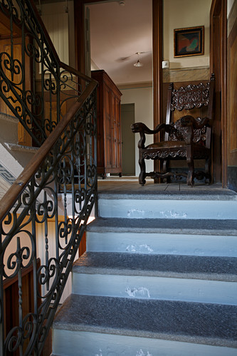 Staircase in villa with antique chair on landing