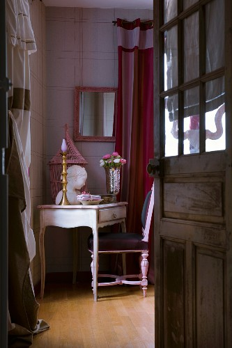 View through open wooden door with glass panels of delicate, antique writing desk with pink, feminine accessories