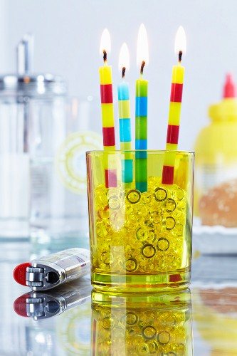 Party candles and decorative pebbles in glass
