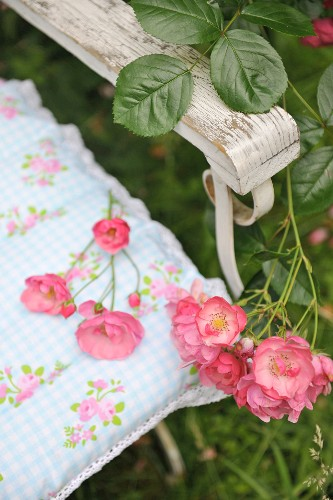 Detail of chair with arm rest and sprays of shrub roses lying on patterned cushion