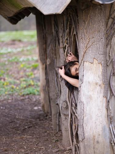 Dark-haired woman in wooden hut