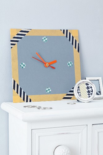 Home-made, cardboard wall clock decorated with patterned tape