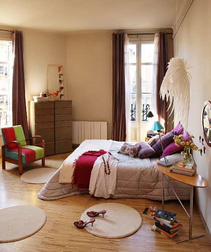 Round rugs around double bed with silver bedspread and vintage chair with colourful upholstery in front of French windows