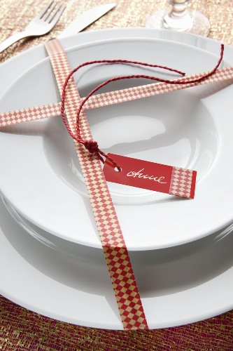 Plates decorated for Christmas with a name tag and wrapped with masking tape