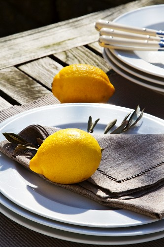 Lemons and stacked plates on rustic table