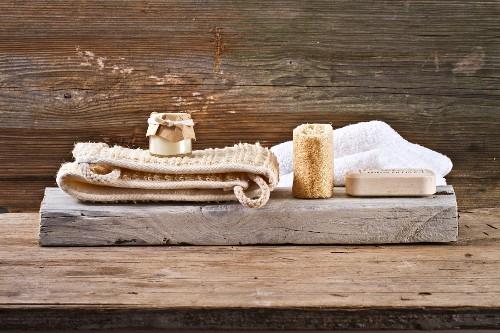 Spa decoration in natural tones - massage belt, natural sea sponge and block of soap on wooden board