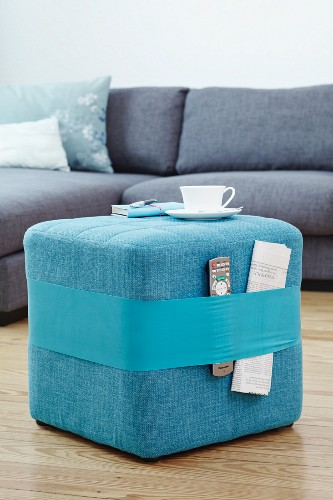 Stool wrapped in wide rubber band for holding newspapers and remote controls