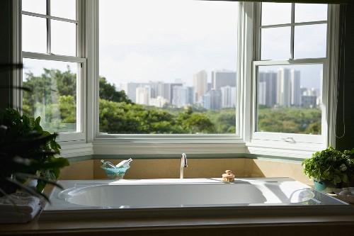 Modern bathtub near window with view of Hawaiian downtown city