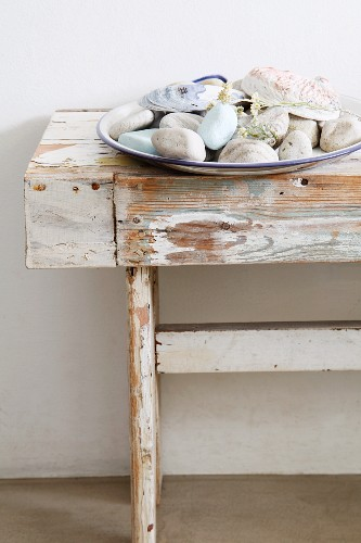 Plate of pebbles and shells on old wooden bench with weathered white paint