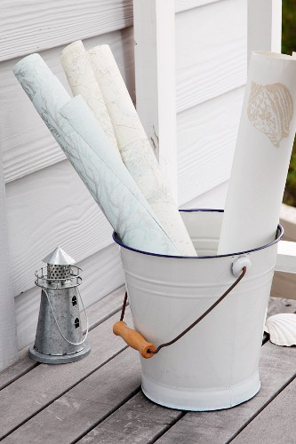 Rolls of paper in enamel bucket and tealight holder shaped like a miniature lighthouse on teak terrace; painted weatherboard cladding in background