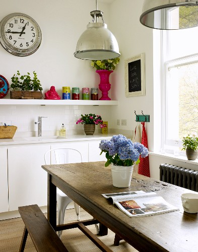 Kitchen with vintage wooden table and bench, above an aluminum hanging light