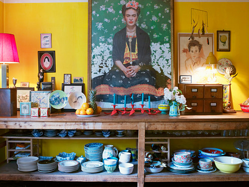 Large self-portrait of Frida Kahlo above middle of open-fronted shelves of crockery surrounded by various pictures and painted china against yellow wall