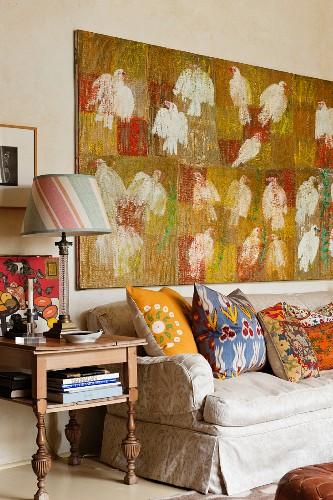 Assorted Kathryn Ireland design cushions on sofa beneath bird artwork