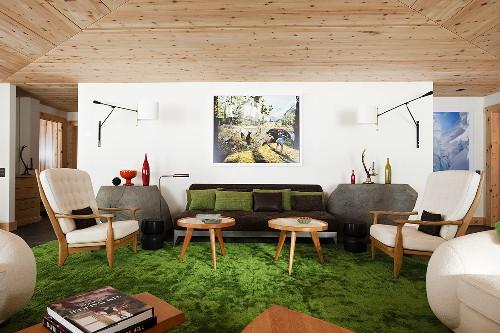 Sessel und Beistelltische im 50er Jahre Stil auf grünem Teppichboden vor Wand mit moderner Wandleuchte im Wohnraum mit Holzdecke
