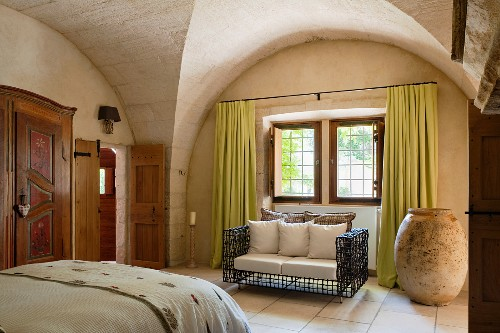 Rustic bedroom with historical stone vaulting; designer sofa with wire frame next to enormous urn