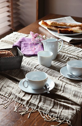 Casually set coffee table with lilac serviettes and earth tone, crash linen fringed blanket
