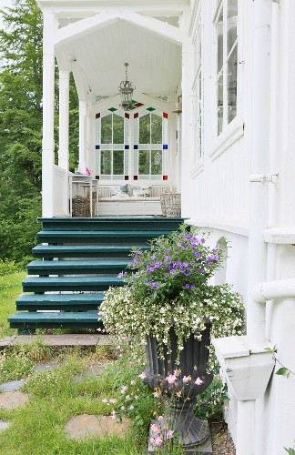 Entrance area with nostalgic, white veranda and wooden steps painted petrol blue behind planted urn