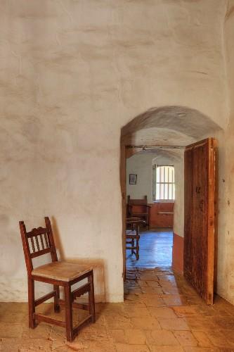 Empty chair gaurds interior doorway of adobe building, Mission La Purisima State Historic Park, Lompoc, California