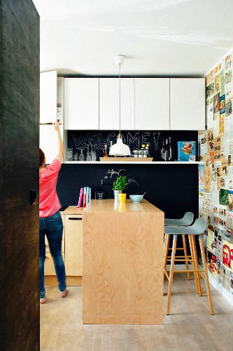 White wall units and kitchen counter next to wall papered with retro magazine clippings