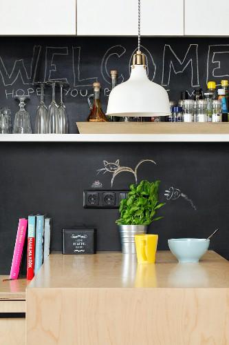 Kitchen counter with chalkboard splashback and white wall-mounted shelf
