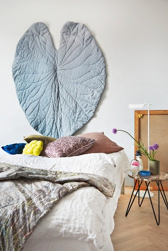Hand-sewn leaf-shaped wall hanging above head of double bed