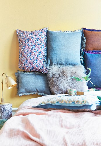 Soft headboard made from various cushions attached to pastel yellow wall