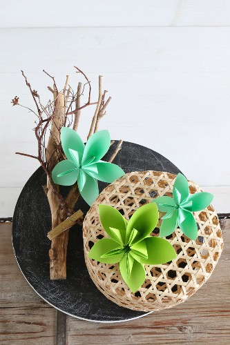 Green origami flowers on top of branch and basket