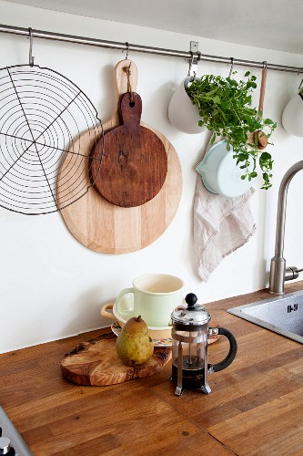 Chopping boards and utensils below row of hooks in kitchen