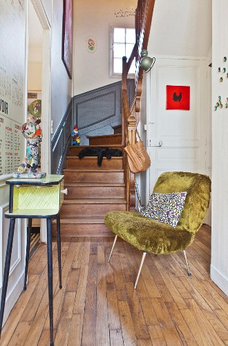 Retro easy chair with faux-fur upholstery in hallway of period building