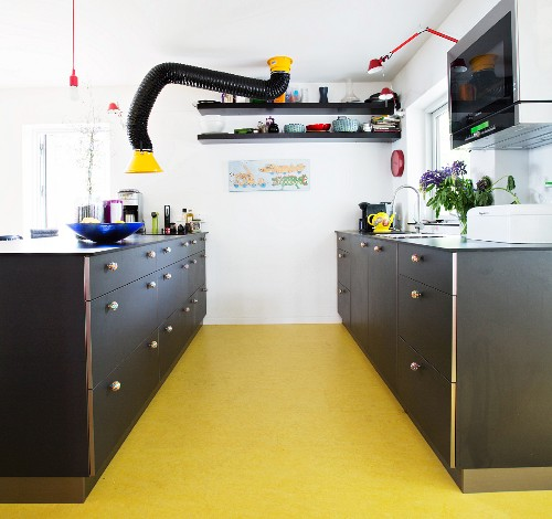 Black furniture and yellow floor in retro kitchen
