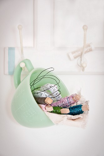 Various reels of wire and tape measure in pastel-green cup