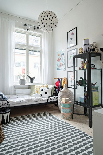 Black and white rug, display cabinet and action figures in boy's bedroom in period apartment