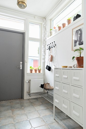 White chest of drawers, coat pegs and grey front door in bright hallway