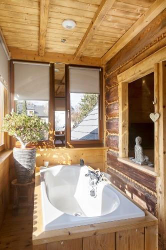Wood-clad white bathtub below interior window in rustic dacha