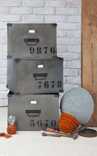 Knitted lightbulb cushion next to stacked metal storage boxes