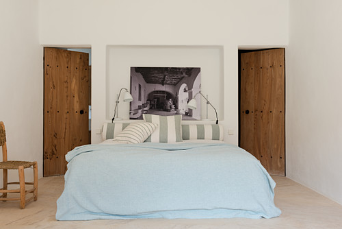 Bed in front of niche flanked by two wooden doors