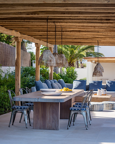 Dining table and lounge area under summery pergola