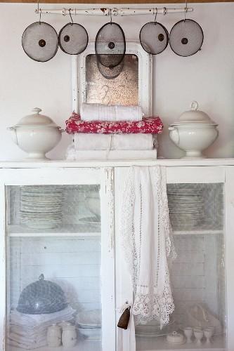 Kitchen utensils in old cupboard with translucent mesh doors