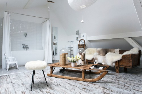 Fur blankets and wooden sledge in rustic lounge area of modern bathroom