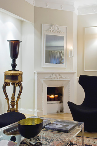 Glass coffee table and designer armchair in front of fireplace and urn on table in elegant living room