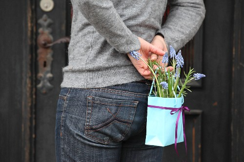 Person holding bag of grape hyacinths behind back