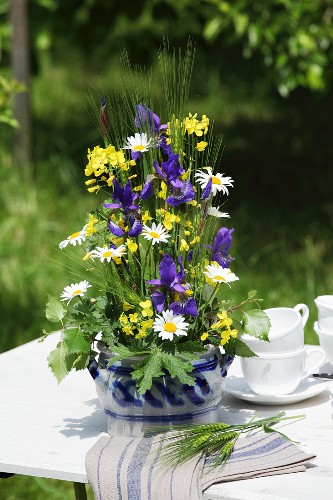 Arrangement of iris, rapeseed and ox-eye daisies in stoneware jar