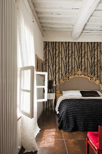 Opulent bed against patterned wallpaper in bedroom with wood-beamed ceiing