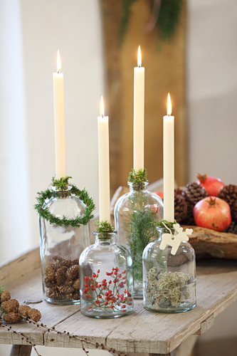 Four lit candles in old glass bottles with natural decorations inside