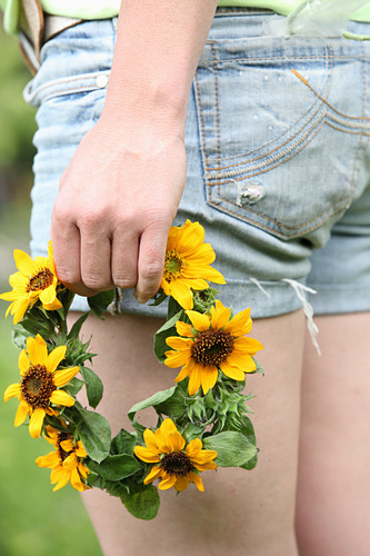 Wreath of sunflowers held in woman's hand