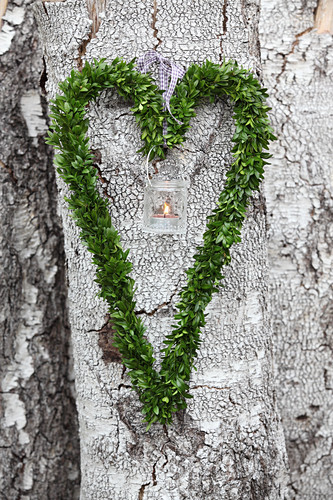 Candle lantern in heart-shaped box wreath hung on tree