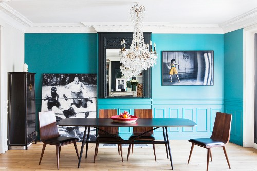 Turquoise wall and crystal chandelier in dining room