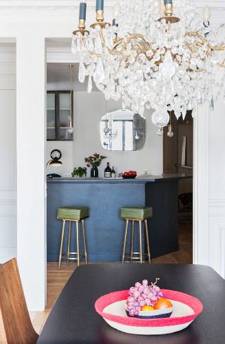 Crystal chandelier above dining table in front of kitchen counter and retro bar stools